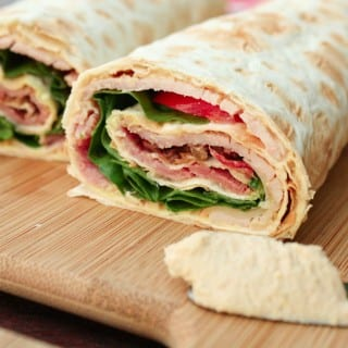 Ham and cheese roll-ups on lavash with hummus and tapenade.