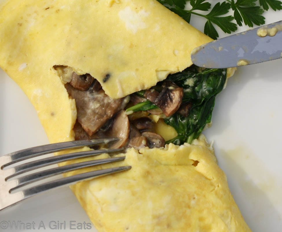A perfect French omelet, with Spinach, mushroom and cheese. | Learn how to make one on WhatAGirlEats.com