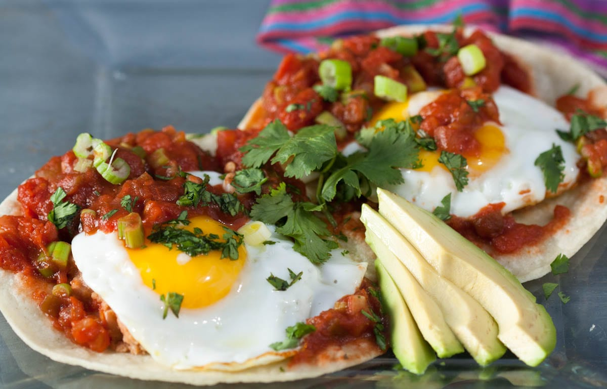 Huevos Rancheros is a popular Mexican dish of fried or poached eggs served on a tortilla with a spicy tomato sauce. Here's the recipe to make them at home! | What a Girl Eats