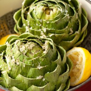 Artichokes ready for steaming with lemon, Italian herbs, kosher salt and olive oil.