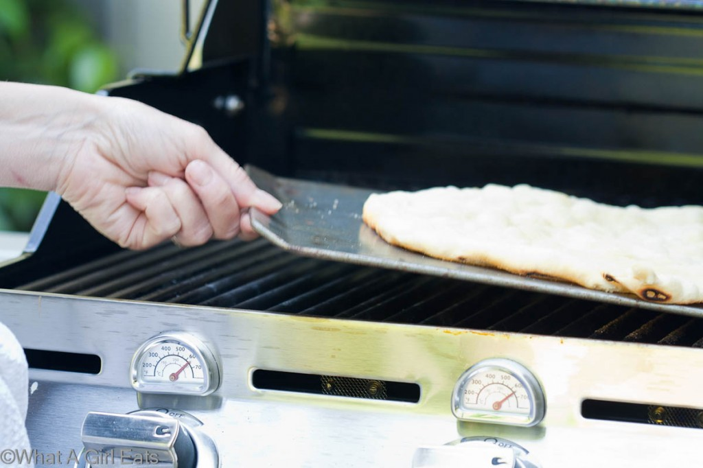 Use an inverted cookie sheet, (without a rim) to slide the pizza on and off the grill.