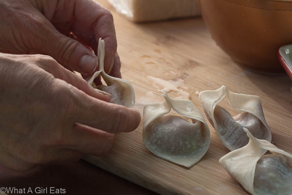 How to make homemade wontons. Pinch the edges of the filled wontons together.