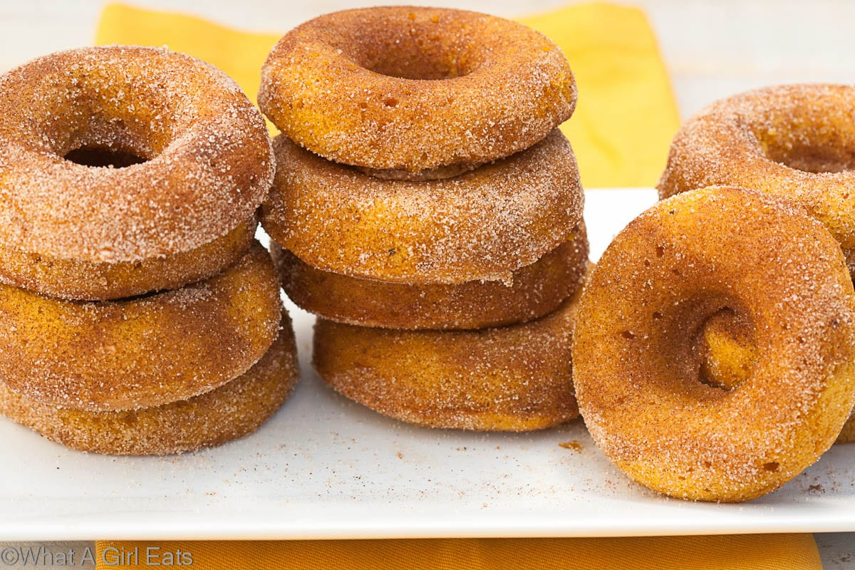 Baked with real pumpkin and warm spices, these pumpkin doughnuts are perfect with a warm cup of coffee or cider! | @whatagirleats