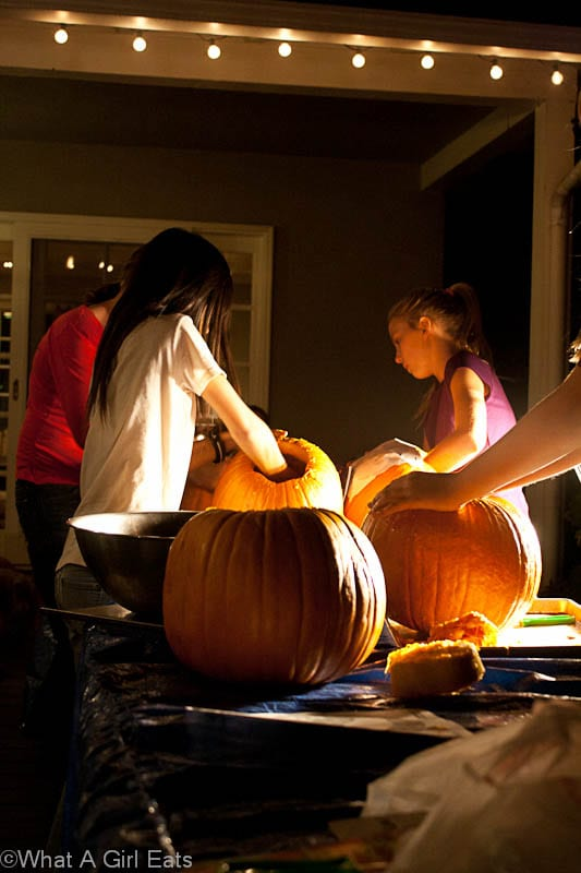 5 girls having a lot of fun with their pumpkin carving activities.