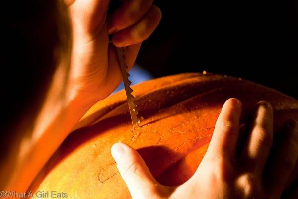 Cutting a design into a pumpkin, using a small awl.