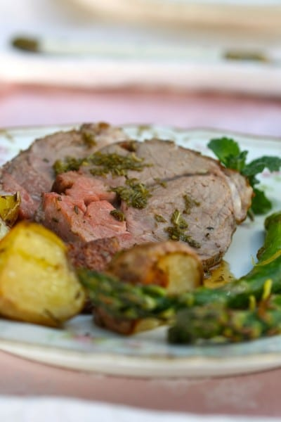 Leg of Lamb with Fresh Mint Sauce is roasted with rosemary and studded with garlic. It's the perfect Easter meal or Sunday supper recipe | @whatagirleats