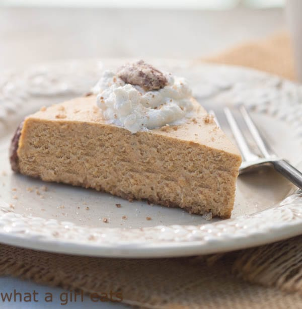 Gluten-free pumpkin spice cheesecake with Bourbon Maple whipped cream and sugared pecans. A delicious fall dessert recipe. | WhatAGirlEats.com
