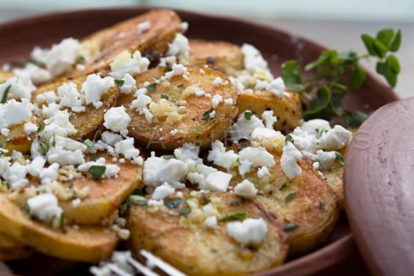 Greek style garlic roasted potatoes with feta. | WhatAGirlEats.com