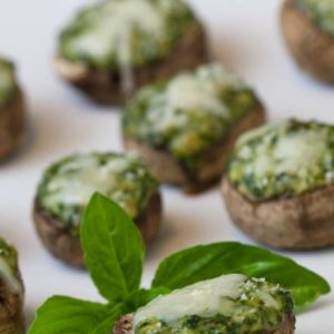 Spinach souffle stuffed mushrooms are an easy but elegant appetizer. Creamy spinach souffle tucked inside of fresh mushroom caps, topped with Parmesan, and baked until golden. | WhatAGirlEats.com