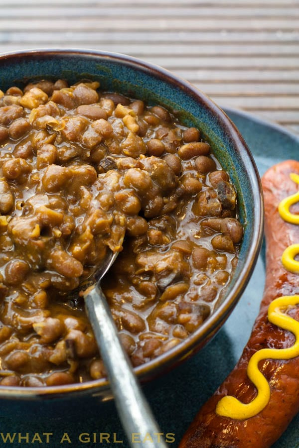 Boston baked beans are a must-have side dish for picnics and potluck dinners. This easy-to-make slow cooker Boston baked beans recipe helps you make them in a snap! | WhatAGirlEats.com