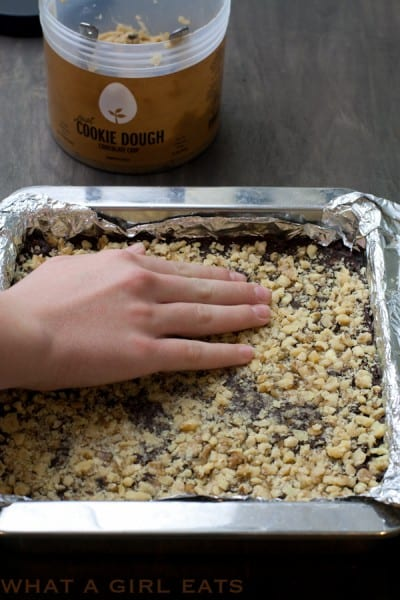 Adding crushed nuts onto the top layer of fudge.