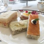 A selection of tea sandwiches including, smoked salmon with caramelized shallot caper cream, chicken salad with orange and cranberry, pickled saffron radish with watercress and dill cream and ham, egg and prosciutto.