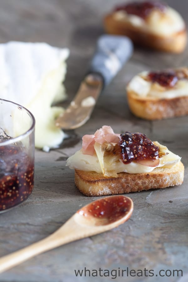 Brie with caramelized onions, prosciutto, and fig jam is an easy-to-make appetizer that works well for all occasions, from dinner parties to game day parties!   WhatAGirlEats.com