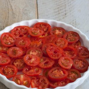 Layer the tomatoes in a tart pan.