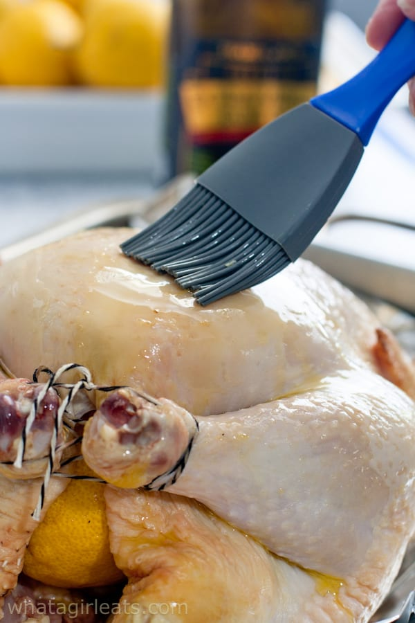 Brushing a chicken with olive oil