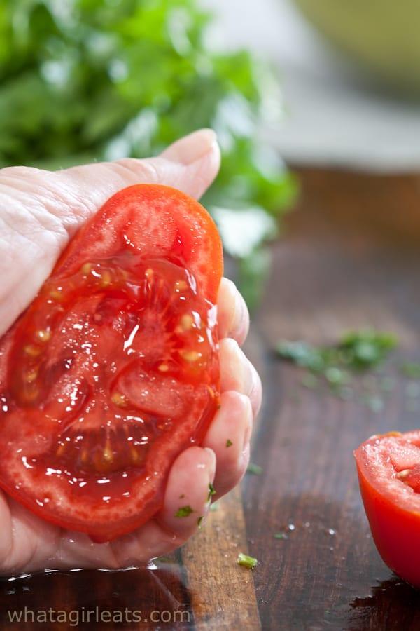 squeezing a tomato half