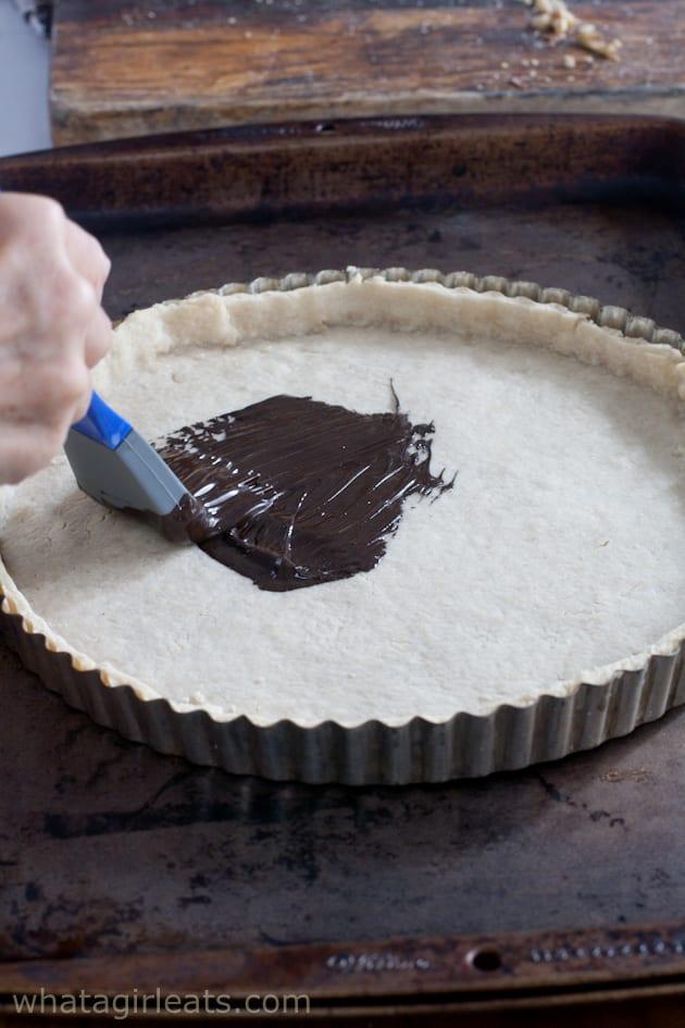 brushing the tart crust with chocolate