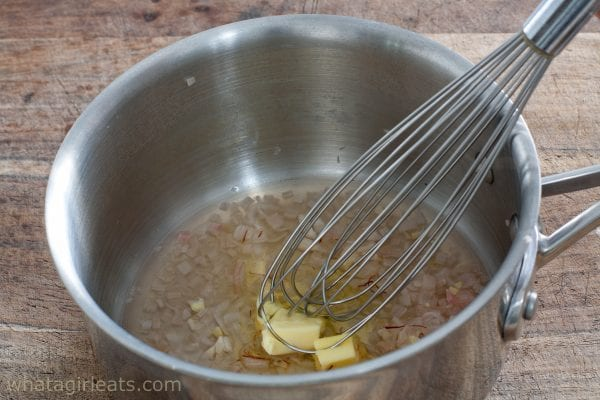 whisking butter into shallots